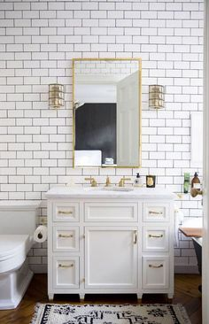 Subway tile with dark grout, inset doors, vanity to look like furniture (with tiny feet), brass hardware, sconces, geometric rug, hardwood floors.