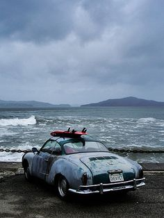 VW Karman Ghia, looks like it's spent most of it's life near the sea.  Love the surfboard on top!