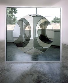 Dan Graham: Triangular Pavilion with Circular Cut-out Variation c, 1989-2001. Two way mirror glass, plain glass, painted aluminium and stainless steel, 205 x 208 cm.