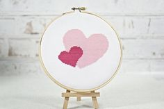 Two pink hearts showing love to everyone. Instant download available in my Etsy shop. Easy cross stitch pattern. Valentine's Day Hoop Art. Hand embroidery.