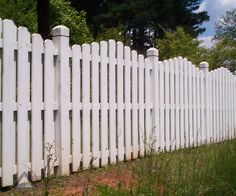 A shadowbox design from Atlanta Decking & Fence creates additional interest to this white privacy fence with gothic posts.