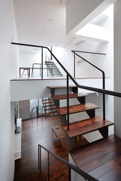 """Multiple open staircases at either end of the skinny house connect these split-level floors, resulting in a series of circulation routes that encourage residents to wander through the house rather than """"moving monotonously within it""""."""