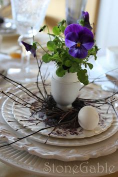 spring loveliness... stacked white plates topped with a bird nest, egg cup, and pansy in an egg shell
