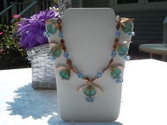 """Green beads with blue, orange and green crystals with copper tone beads and copper strips . 19"""""""