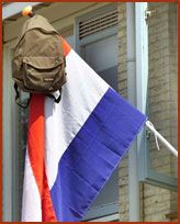 This is a tradition in the Netherlands, where students who got their certificate of the secondary school, hoist the flag together with their schoolbag and books.
