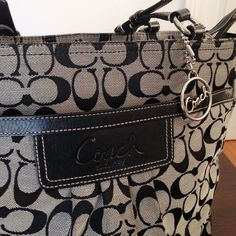 AUTHENTIC COACH Print Shoulder Bag Gently worn. Slight wearing on bottom corners and minor staining on inside of bag. Black and gray coach print on outside. Front and back of back both have outside compartments and inside back is one big zipped compartment. Blue lining on inside. 100% authentic Coach Bags
