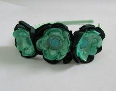 Tiara forrada com fita de cetim, com três flores de cetim em tons de verde.