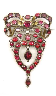 18th century garnet cluster pendant brooch, c.1760, designed as a ribbon tied bow suspending an openwork heart with central swing drop and smaller swing drop below, close set in silver with oval faceted and rose cut garnets