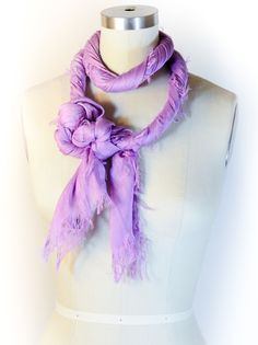 Instructions:We think this unique knot looks like a bunch of grapes — Carmen Miranda would approve. This style sure is a sweet treat for your wardrobe.  Whether you think this knot looks like a bunch of grapes or a bundle of baubles, this is a truly creative way to wear your scarves!  Shop the Stacey Fringe Scarf>  Step 1: Place your scarf at the back of your neck centered. Start twisting your scarf until almost the entire length of it is twisted. It will start trying to curl around itself…