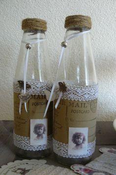 Leuke gepimte flessen met poststempels, kant, lint en een leuk plaatje geprint op canvas.