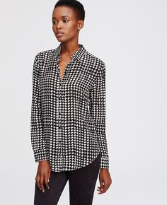 Check mate: exude timeless sophistication with our flattering houndstooth blouse, indulgently rendered in luxe silk. Point collar. Long sleeves with button cuffs. Button front. Back yoke with box pleat. Shirttail hem.