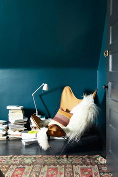 dark walls with light furniture, red, yellow, navy, fur blanket on collapsible chair, piles of books with thin metal light