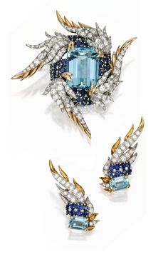 PLATINUM, 18 KARAT GOLD, AQUAMARINE, SAPPHIRE & DIAMOND BROOCH & MATCHING EARCLIPS, SCHLUMBERGER FOR TIFFANY & CO. The brooch centered by an emerald-cut aquamarine accented by 59 round sapphires, framed by four stylized wings decorated with round diamonds, signed Tiffany Schlumberger; a pair of stylized wing earclips set with two emerald-cut aquamarines accented by 16 round sapphires, further set with round diamonds, one earclip signed Tiffany, the other signed Schlumberger; circa 1960.