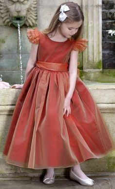 Love! NICKI MACFARLANEBurnt Red Silk Organza Ballerina 'Francesca' Dress. In a stunning shade of 'Firecracker' burnt orange/red, this full and voluminous dress has a fitted bodice with organza ruffle capped sleeves. The ballerina length skirt is gathered and full, with a layer of silk chiffon underneath and further underskirts of stiff tulle petticoats which add volume.