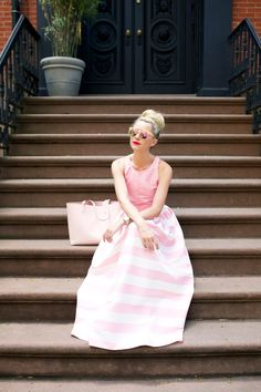 I love this. Pink and white striped full skirt, sleeveless pink top, topknot, pink sunnies, pretty red lips, white nails
