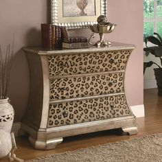 Every home should have a piece in their home that creates drama and interest. This accent cabinet will do just that with its diva-like leopard print on the three front drawers. Surrounding the sides, edges and top is a hand-painted gold that gives a modern, upscale vibe. With a arched side shape, gold finish and leopard print, this accent cabinet is sure to become an attractive piece in your entryway, living room, or bedroom.