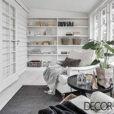 O aconchegante e acolhedor espaço traz poltrona em tom branco e mesa de apoio escura com adornos