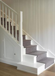 The stairs are painted in white and blends in with the wall. A run mode follows the middle of the stairs all the way up. This is both a practical and aesthetically pleasing solution, the stairs are more majestic while preventing slipping on the steps. Behind the doors under the stairs owners have room for storage.
