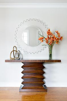 An exotic wood table with a graphic accordion base is topped with a round acrylic mirror, creating an entryway with fun, contemporary flair. A tall vase of bold orange flowers is counter-balanced by a low but weighty metal sculpture, forming an asymmetric arrangement that's clean and simple.