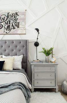 This silver nightstand was a DIY that works perfectly in this modern master bedroom. Love that gray tufted headboard!