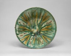 Bowl with Green, Yellow, and Brown Splashed Decoration (Object Name: Bowl Date: 10th century Geography: Iran, Nishapur Culture: Islamic Medium: Earthenware; white slip, incised and splashed with polychrome glazes under transparent glaze (sgraffito ware) Dimensions: H. 2 7/8 in. (7.3 cm) Diam. 10 1/4 in. (26 cm) Classification: Ceramics Credit Line: Rogers Fund, 1938)