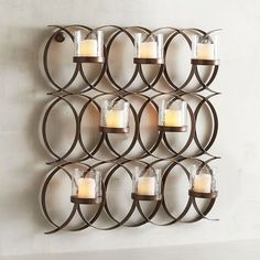 Featuring eight clear glass candle holders, our wrought iron sconce of intertwining circles makes quite an impact on any wall. Handcrafted, then hand-painted with a bronze finish, it will add a modern vibe to the romantic ambience created by your favorite votives.