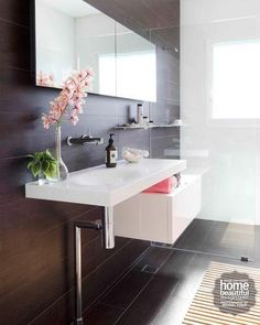 A floating Minosa basin and a display shelf are positioned asymmetrically on the wall to create a floating feature.