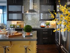 Rich, espresso-stained wood cabinets provide a dark backdrop to this kitchen's sunny yellow island. Sustainable materials, like a mosaic backsplash made from reclaimed stained glass, quartz countertops, energy-efficient appliances and low-voltage lighting make this HGTV Green Home kitchen as eco-friendly as it is beautiful.