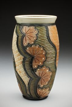 This vase was thrown from stoneware clay, trimmed, and hand decorated with a floral pattern after several days of drying.  Slips were painted onto the bisqued clay, and the vase was fired to cone 1...