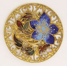 A blue floral design crafted in champlevé enamel decorates this pierced openwork brass button. Red and green champlevé enamel leaves add further color accents.