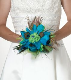 """This exquisite 9"""" bouquet combines peacock feathers with aqua feathers, green satin and green tulle. The middle flower is decorated with a rhinestone ornament. A 4"""" long clear acrylic handle allows fo"""
