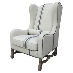 Breezy and beautiful, this wood-framed wingback arm chair is wrapped in off-white linen upholstery accented with an indigo stripe. A complementing bolster pi...