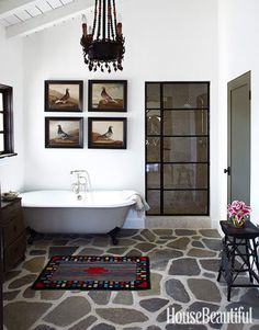 """Spanish Bathroom The bathroom floor in this Spanish-style California house is made of Ojai river rock. """"It's so strong, you could build a Hyatt Regency on it,"""" designer Kelley McDowell says. She designed the shower door in the style of a metal casement window. Shower faucet by Sunrise Specialty. Cast-iron tub from the Tub Connection."""