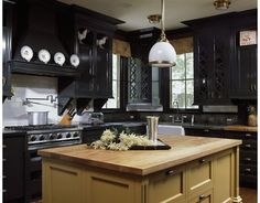 Subtle mustard on the island lightens the banks of black cabinetry and elevates the feel of this kitchen.