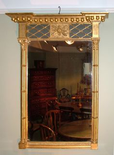 A large early 19th century Regency period carved giltwood pier glass Mirror, having breakfront cornice with ball decoration above lattice work panel with central stylised sunburst. The Mirror flanked by Corinthian cluster columns and acanthus moulded bottom rail.  Circa: 1825