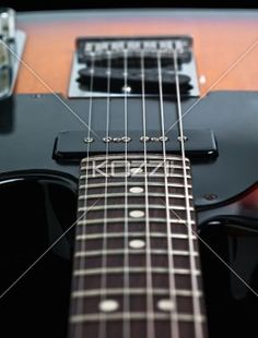 cropped image of a fret board and strings. - Detailed cropped shot of strings of fret board on electric guitar.