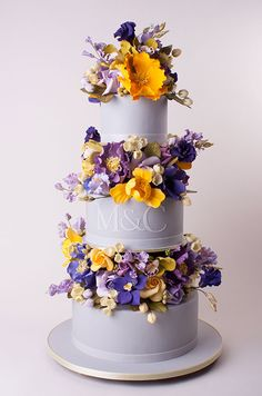 Three layers of wedding cake are separated by two layers of fabulous sugar flowers. Not keen on the colours but nice design.
