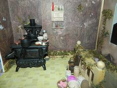 My Faerie House. Kitchen. Stove is an antique demo, popsicle stick shelves, some of the food and dishes are sculpey, others are from dollhouses. The glass bottles on the shelf are from glitter nail decorations (some of which I left in the bottles) that I got from the Dollar Tree.