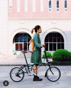 Young woman wearing a green coat rides a Brompton bike in a city See other ideas and pictures from the category menu…. Faneks healthy and active life ideasRead More → Buy Bike, Bike Run, Road Bike, Bicycle Women, Bicycle Girl, Brompton, Velo Vintage, Urban Cycling, Folding Bicycle