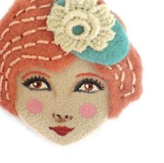 Inspired by the playful yet stylish fashion of the 1920s, this felt brooch will add a unique touch to your accessory collection.    This felt brooch is handcrafted with great attention for details. It is handmade with felt and ultra suede fabrics. The hair is made with a beautiful grapefruit felt and decorated with embroidery. The facial features are hand painted with acrylic colors.    If you are looking for a unique handmade gift to give to your mother, wife, sister or friend – this art…