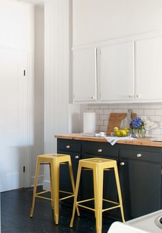 I'm kinda liking the dark lower cabinets and white upper cabinets. Also the white subway tile (of course!). Plus, how cute are those yellow stools?!