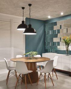 Sala de jantar linda com destaque para a cor da parede e para o painel espelhado. A mesa e as cadeiras conferiram leveza ao ambiente. Projeto Angela Meza