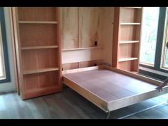 Murphy Bed (Wall Bed) hidden behind two bookshelves that push aside to reveal bed unit.