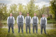 Simple and casual groomsmen attire; grey suit with blush ties. Groom with ivory tie.