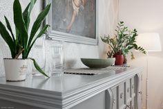 Harmoniaa ja romantiikkaa vanhassa omakotitalossa - Ruokailutilaa hallitsee suuri massiivipuinen pöytä tuoleineen. Kaksi modernia kattovalaisinta sopii hyvin pöydän päälle ja paitsi että ne valaisevat tarpeeksi ne myöskin tasapainottavat mittasuhteita. Vihreät kasvit virkistävät huonetta ja suuren harmaan senkin päälle oleva tummasävyinen taulu toimii vastaparina olohuoneen tauluille.
