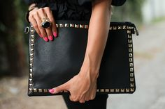 pink nails, black studded clutch, love the ring