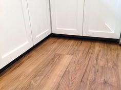 A photo from Home Depot reviewer. Traffic Master Lakeshore Pecan with the white cabinets