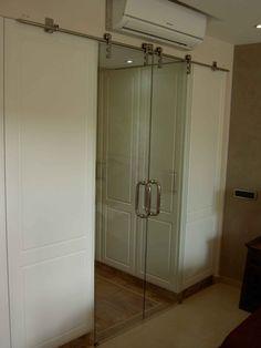 Puerta de cristal  de corredera con herrajes en acero inoxidable para vestidor. Tenerife