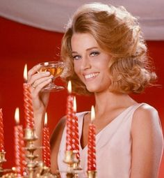Jane Fonda US actress wearing a pink sleeveless top posing with a champagne coupe beside a candelabra with lit candles in a studio portrait against a. Jane Fonda Barbarella, Us Actress, Lady Jane, Jane Seymour, Classic Movie Stars, Iconic Women, Vintage Glamour, Vintage Style, Classic Hollywood