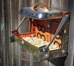 Lixe e pinte as latas ou cubra toda a volta com corda sisal utilizando cola quente. Fixe um suporte de madeira ou metal para servir de apoio ao pássaro enquanto se alimenta. Crie uma casinha utilizando um funil como telhado e tampe o buraco do funil com uma rolha. Para criar comedouros com placas de metal, dobre-as e faça alguns furos, fixe com porcas e parafusos. Você também pode utilizar formas e talheres.